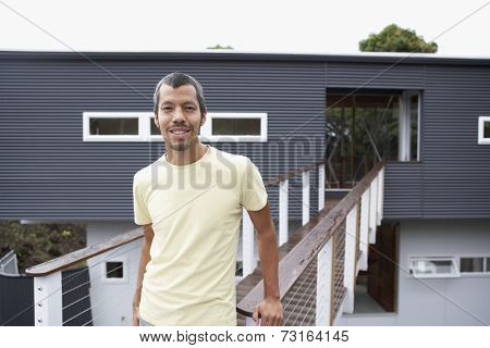 Native American man in front of house