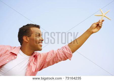 Hispanic man holding starfish