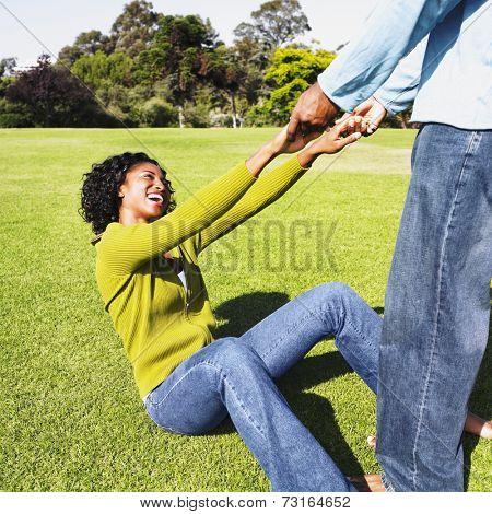 African man helping girlfriend up off grass