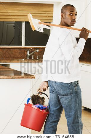 African American man carrying cleaning bucket and mop