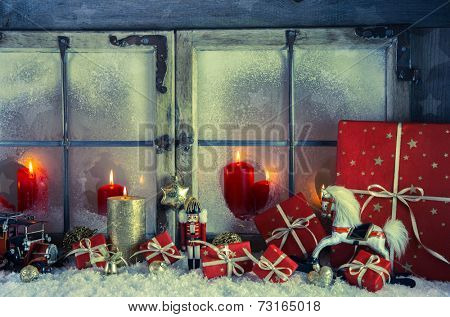 Classical xmas decoration in red and golden colors: rustic old wooden window with candles for a background.