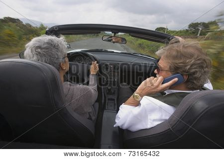 Senior couple driving in convertible car