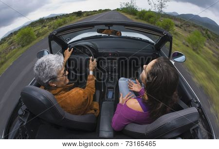 Mother and adult daughter in convertible car