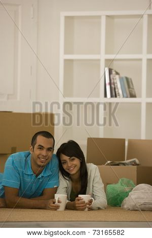 Young couple next to unpacked moving boxes