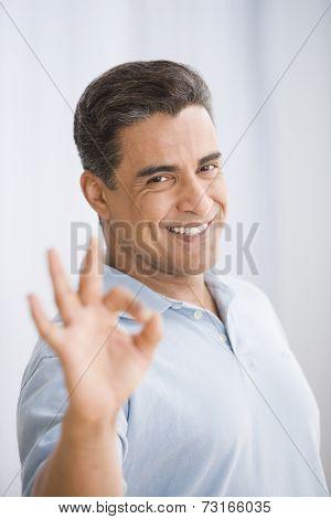 Hispanic man making okay hand gesture