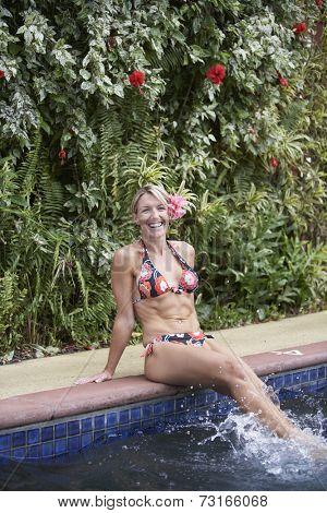Woman with flower in hair splashing in swimming pool