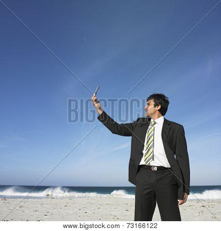 Hispanic businessman looking at cell phone at beach