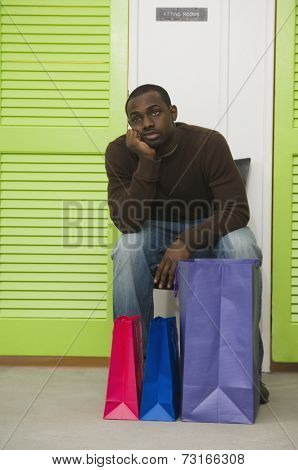 African man waiting outside dressing rooms