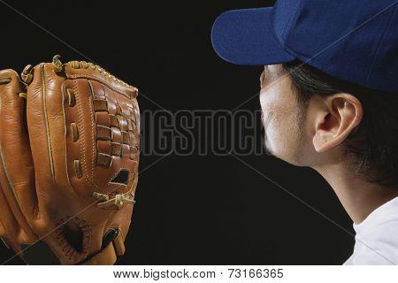Asian man wearing baseball catcher's mitt