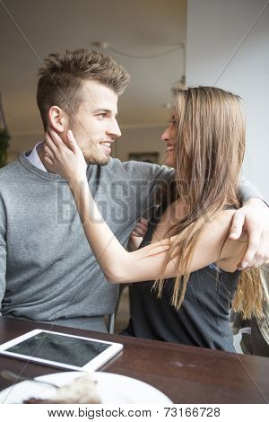 Romantic young couple looking at each other in cafe