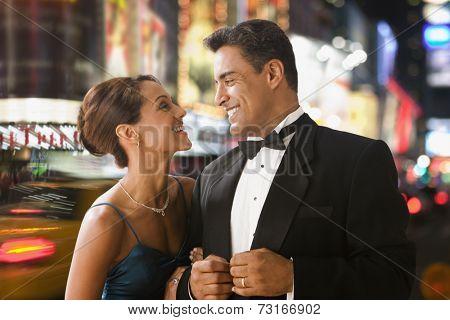 Hispanic couple in eveningwear in urban scene