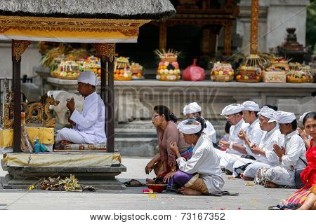 SEPTEMBER 18, 2014 - BALI, INDONESIA: Hindu devotees pray at the Tirta Empul Temple led by a high priest.  Hinduism is the religion of the majority of the Balinese people.