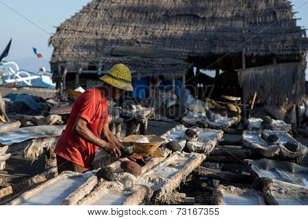 SEPTEMBER 18, 2014 - BALI, INDONESIA: A worker scoops the salt grains from the evaporation platforms after the drying process. Sea salt manufacturing is a traditional cottage industry of Bali.