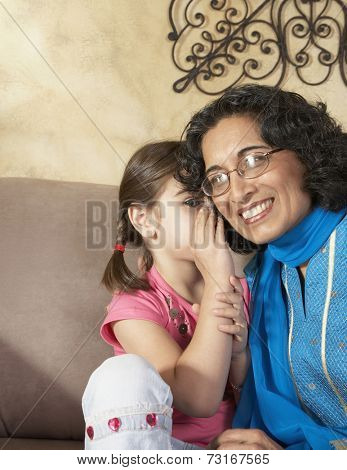 Middle Eastern girl telling grandmother a secret