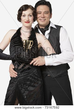 Multi-ethnic couple holding tango trophy