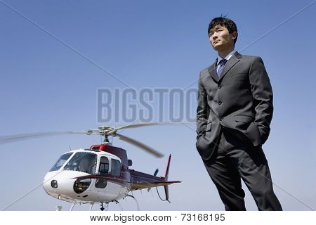 Asian businessman next to helicopter