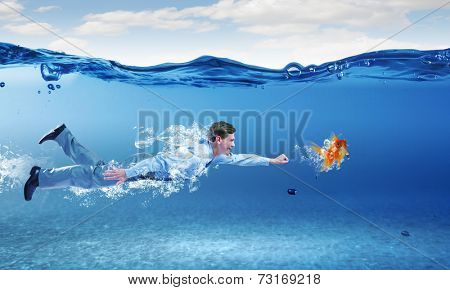 Young businessman in suit swimming under water