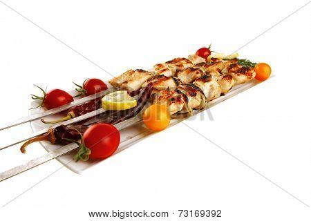 fresh grilled shish kebab on white platter