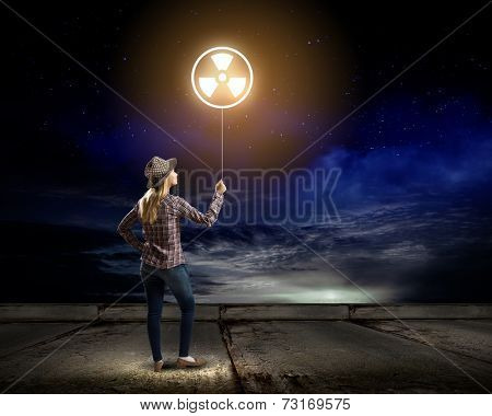 Young woman in casual holding balloon with radioactivity sign