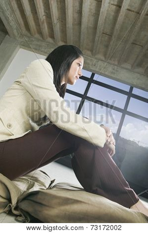 Hispanic woman sitting with hands on knees