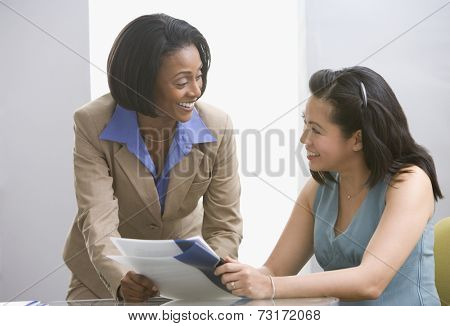 Multi-ethnic businesswomen discussing paperwork