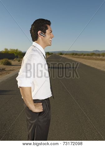 Hispanic businessman using hands free device