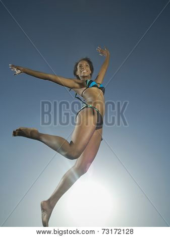 African American woman in bathing suit jumping