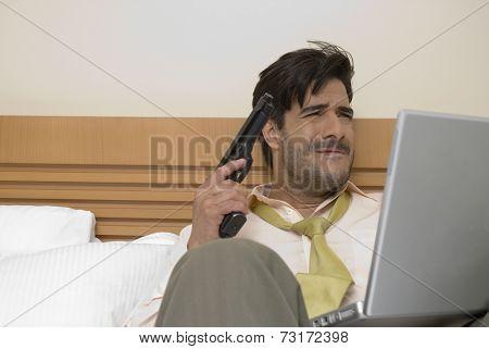 Hispanic businessman holding gun and laptop