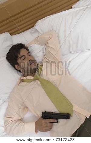 Hispanic businessman holding gun in bed