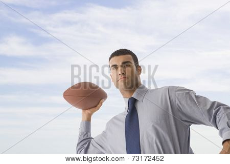 Hispanic businessman throwing football
