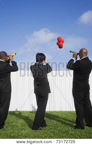 Multi-ethnic businessmen looking over fence at balloons
