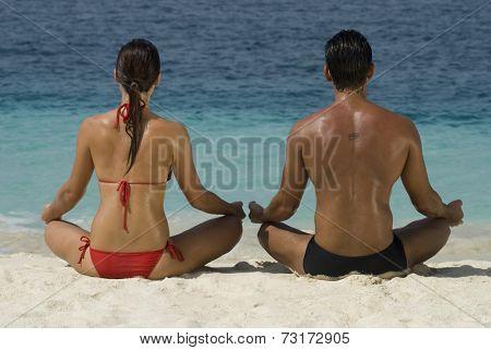 Multi-ethnic couple meditating at beach