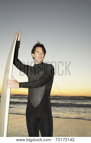 Mixed Race man in wetsuit with surfboard