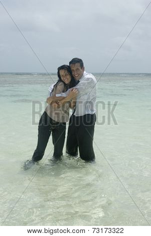 Hispanic businesspeople hugging in water