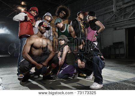 Multi-ethnic breakdancers posing in warehouse