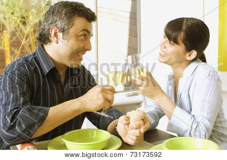 Hispanic couple toasting with wine