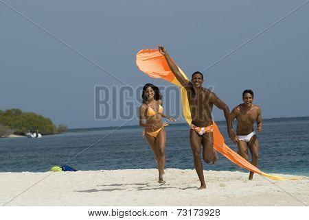 Hispanic friends flying kite at beach