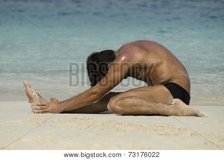 Hispanic man stretching on beach