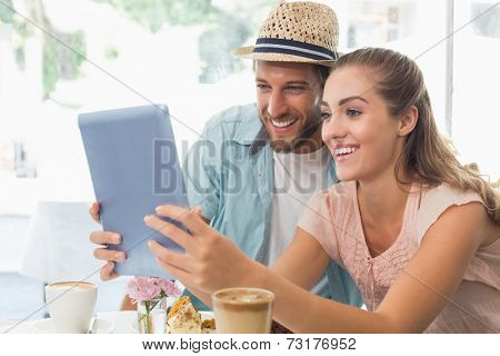 Happy couple enjoying coffee using tablet at the coffee shop