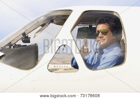 Man giving thumbs up in cockpit of airplane