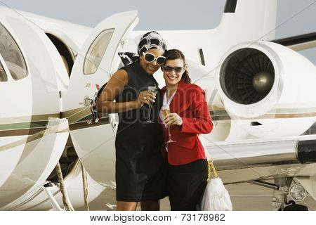 Multi-ethnic women with cocktails next to airplane