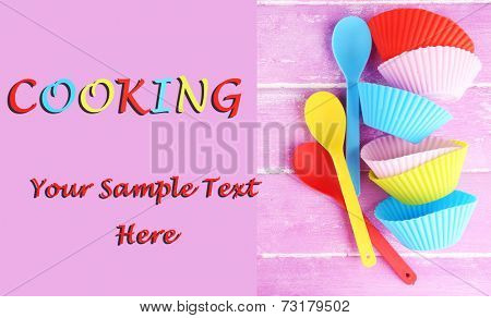 Plastic bowls and spoons on color wooden background