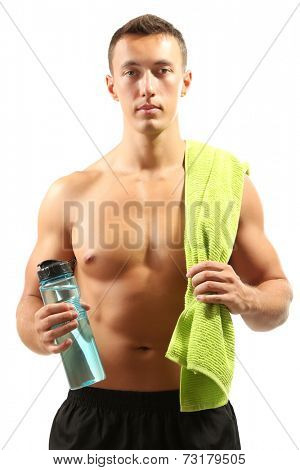 Handsome young muscular sportsman holding towel and bottle with water isolated on white