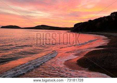 waves on the beach against red sunset of russian isle Putyatin