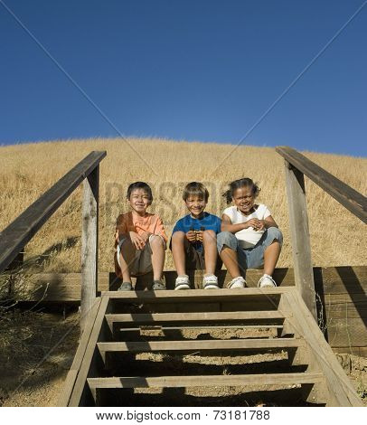 Multi-ethnic children sitting on steps