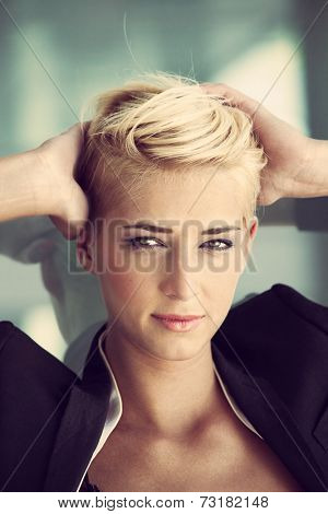 young blue eyes woman with trendy short blonde hair  outdoor portrait recline on glass window hands in hair