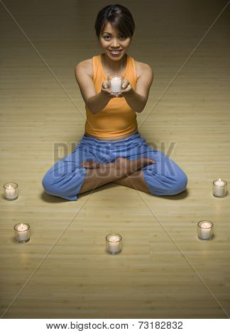 Pacific Islander woman holding lit candle