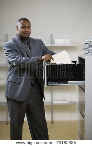 African American businessman looking in file cabinet