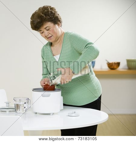 Senior Asian woman making rice