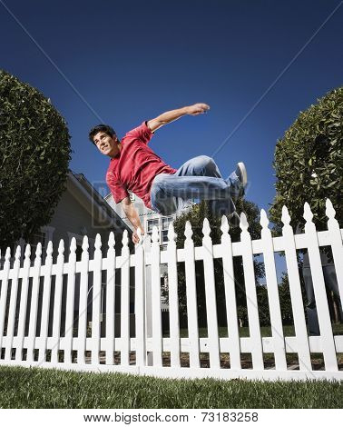 Hispanic man jumping over fence